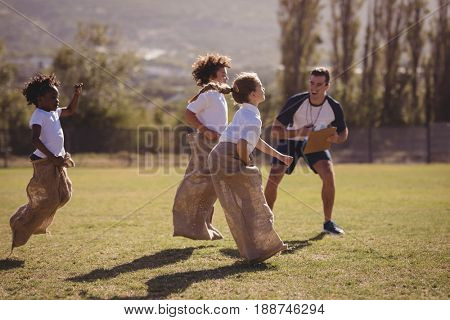 Coach cheering schoolgirls during sack race in park on a sunny day
