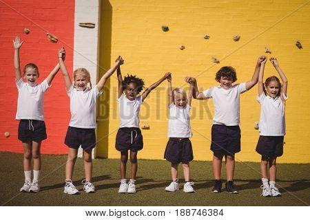 Happy schoolgirls standing with hand in hand in schoolyard