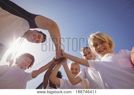 Portrait of happy coach and schoolkids forming handstack in schoolyard