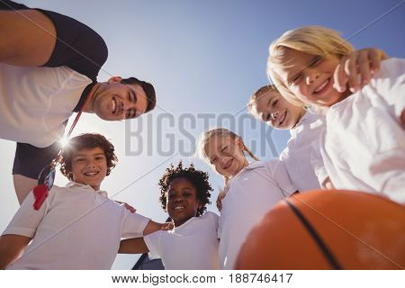 Portrait of smiling coach and schoolkids in schoolyard