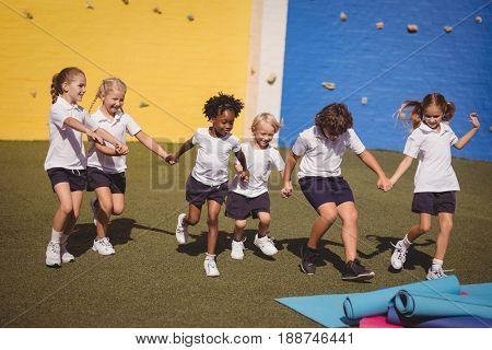 Schoolgirls running with hand in hand in schoolyard