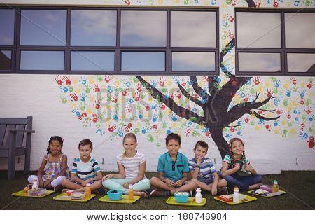 Portrait of happy schoolkids having meal in school