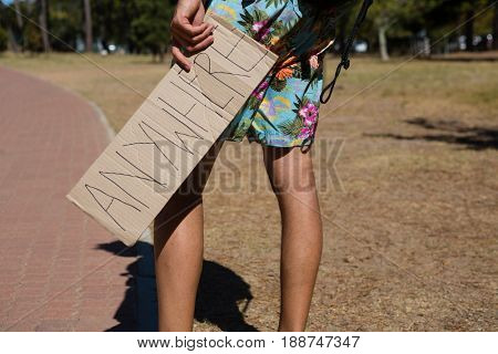 Low-section of man holding cardboard with text anywhere written on it