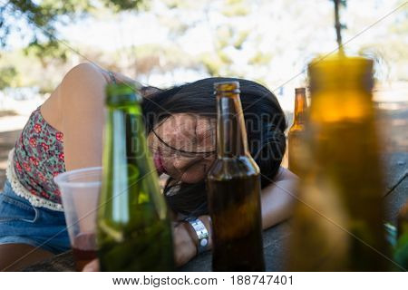 Drunken woman sleeping on the table and holding a glass of beer in the park