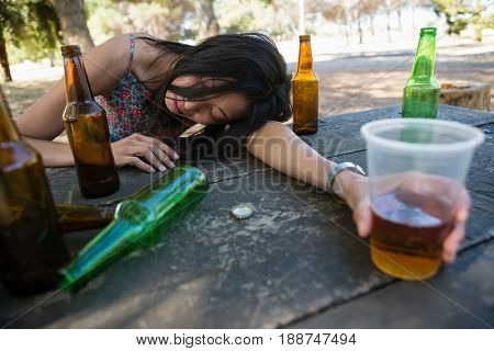 Drunken woman relaxing on the table holding a glass in the park
