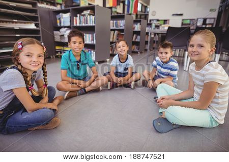 Portrait of happy schoolkids sitting in library at school
