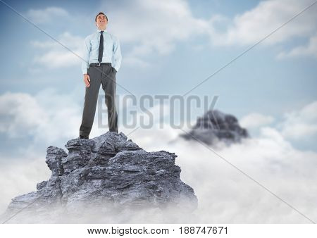 Digital composite of Business man hand in pocket on mountain peak in clouds
