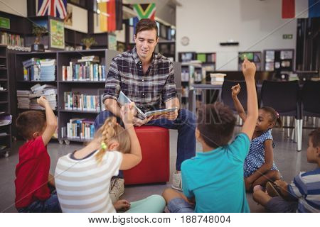 Schoolkids raising their hands while teacher teaching in library at school