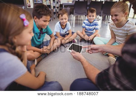 Teacher and schoolkids using digital tablet in library at school