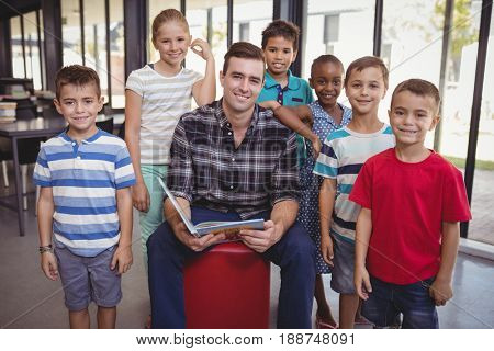 Portrait of teacher and schoolkids in library at school