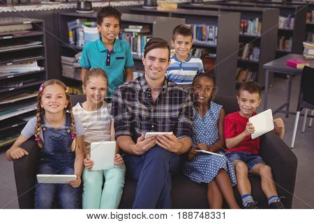 Portrait of happy teacher and schoolkids sitting with digital tablet in library at school