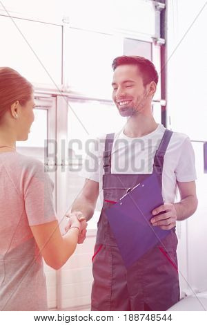 Smiling automobile mechanic shaking hands with female customer in automobile repair shop
