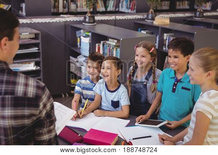 Happy schoolkids interacting with teacher in library at school