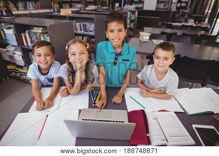 Portrait of schoolkids using laptop in library at school