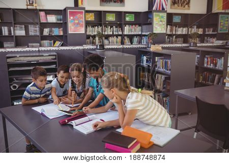 Attentive schoolkid using digital tablet in library at school