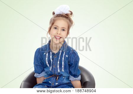 The little blonde girl with a large white bow on the head and short denim dress.She poses on a revolving chair.