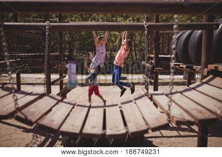 Schoolkids playing on monkey bar at school playground