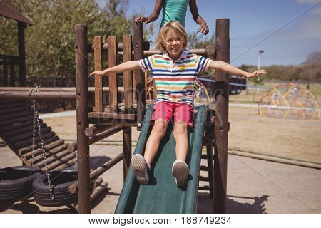 Schoolboy enjoying while playing on slide at school playground