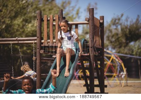 Girl playing on slide at school playground