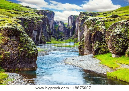 Steep cliffs, overgrown with green moss, surrounded by a very river with cold water. Canyon Icelandic fairy tales and legends - Fyadrarglyufur