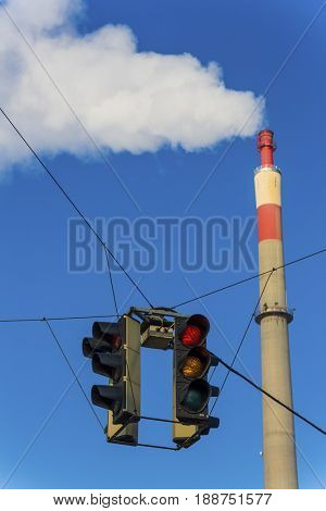 industrial chimney and red traffic light