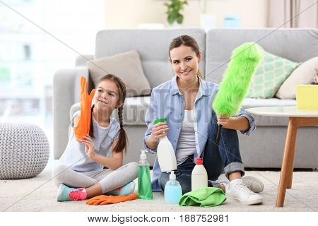 Mother and daughter with cleaning supplies at home