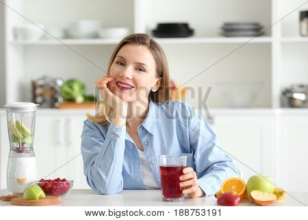 Beautiful woman with glass of fresh juice in kitchen