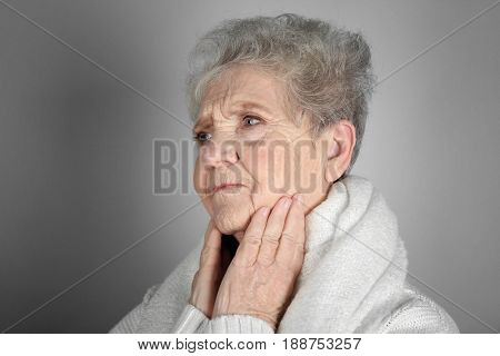 Senior ill woman with sore throat on grey background. Concept of allergy