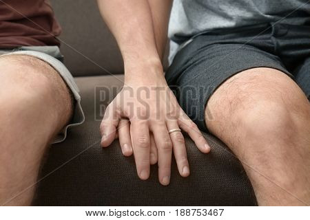 Two homosexuals sitting on sofa and holding each other hand, close up