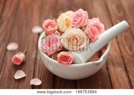 Beautiful spa composition with flowers in bowl on wooden table