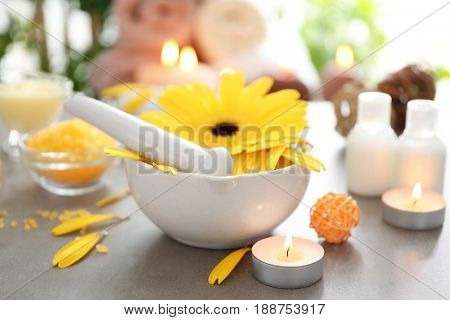 Beautiful spa composition with flower in bowl and candles on table