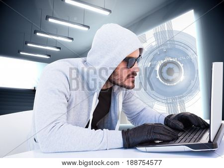 Digital composite of Criminal in hood on laptop in front of interface