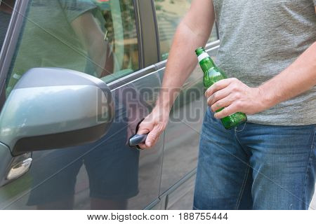 Man opening his car while holding a bottle of beer. Don't drink and drive concept