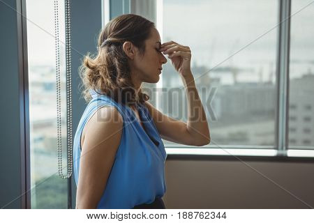 Tensed executive standing near window in office