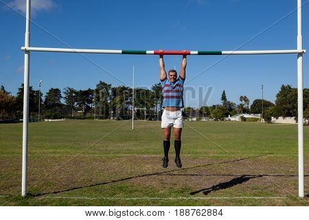 Full length of rugby player hanging on goal post at playing field during sunny day