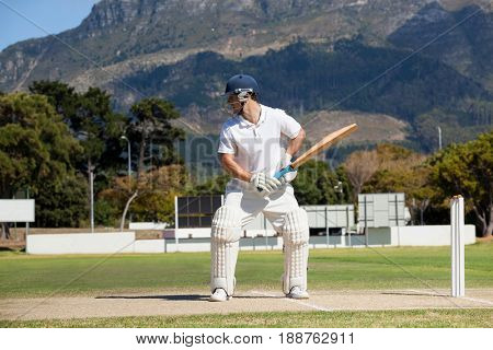 Batsman playing cricket on field against mountain during sunny day