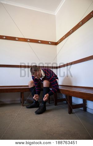 Rugby player tying sportsashoes while sitting on bench in locker room