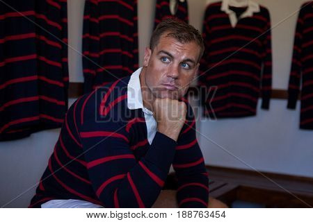 Thoughtful rugby player with hand on chin sitting on bench against clothes rack in locker room