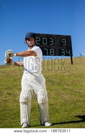 Confident cricket player swinging bat while standing against scoreboard at field