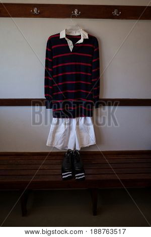 Shoes and socks on wooden bench against rugby uniform hanging from wall