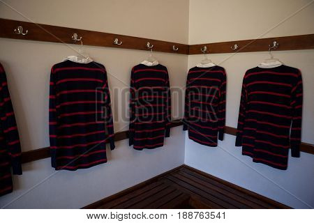 Rugby shirts hanging from clothes rack in locker room