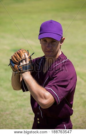Portrait of confident baseball player wearing gloves standing at field