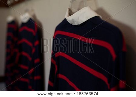 Close-up of rugby shirts hanging in locker room
