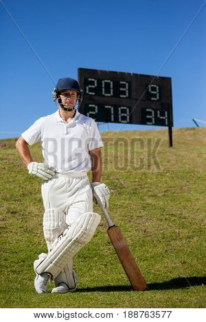 Full length of confident cricket player with bat standing against scoreboard on field