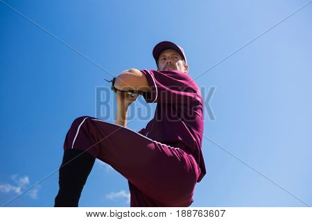 Low angle view of baseball pitcher throwing ball against blue sky on sunny day