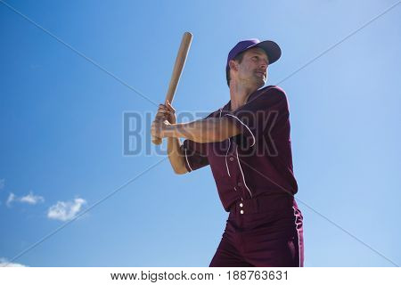 Low angle view of young baseball player holding bat against blue sky on sunny day
