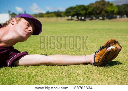Baseball pitcher catching ball while diving on field during sunny day