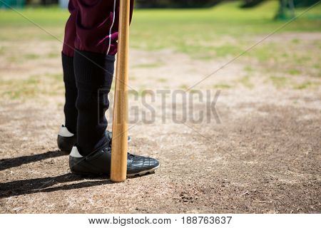 Low section of baseball player holding bat while standing on field during sunny day