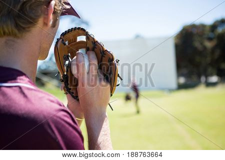 Baseball pitcher holding ball in glove at playing field on sunny day