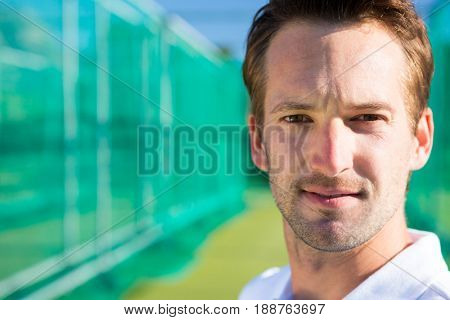Close up portrait of young cricketer against net on field